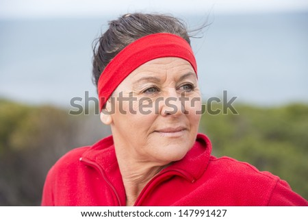 Portrait attractive middle aged woman, happy, relaxed, sporty, friendly, positive, successful, enjoying active retirement outdoor, wearing red sweater and headband, with blurred background. - stock photo