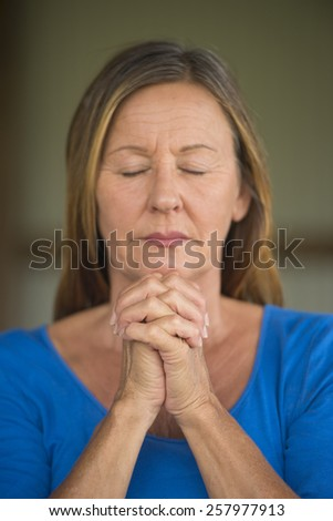 Portrait attractive religious christian mature woman praying with folded hands, thoughtful, hopeful, meditating, blurred background, copy space. - stock photo