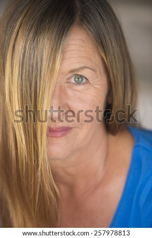Portrait attractive woman with brunette hair covering half face, one eye confident friendly upward look, blurred background. - stock photo