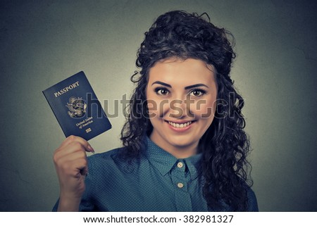 Portrait attractive young excited woman with USA passport isolated on gray wall background. Positive human emotions face expression. Immigration travel concept   - stock photo