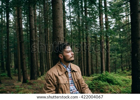 Portrait bearded man hipster sits dream in mountain green forest - stock photo