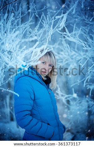 Portrait Beautiful Attractive Young Woman in Wintertime outdoor in the snow-covered wood - stock photo