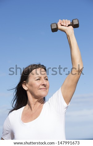Portrait beautiful confident middle aged woman exercising with weights, keeping relaxed healthy and fit, focused view, determined, positive, successful, with blue sky as background and copy space. - stock photo