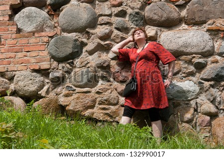 Portrait beautiful happy middle aged woman standing  relaxed on sunny day outdoor wall - stock photo