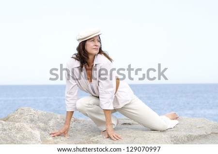 Portrait beautiful looking confident mature woman sitting on rock at ocean outdoor, enjoying active retirement, isolated with sea and cloudy white sky as background and copy space. - stock photo