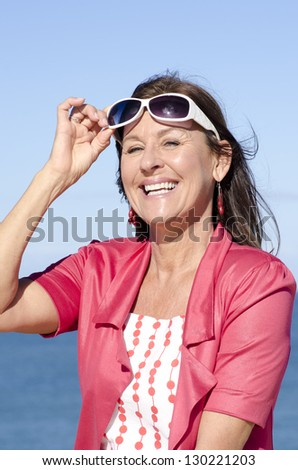 Portrait beautiful mature woman happy smiling and arms up behind neck, joyful outdoor sunny day, isolated with ocean and blue sky as background. - stock photo