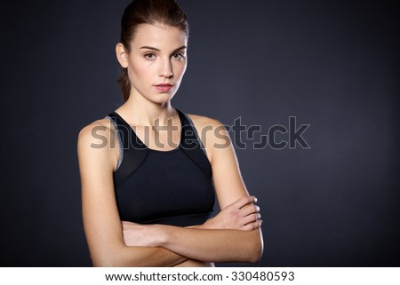 Portrait beautiful young athletic girl on a black background - stock photo