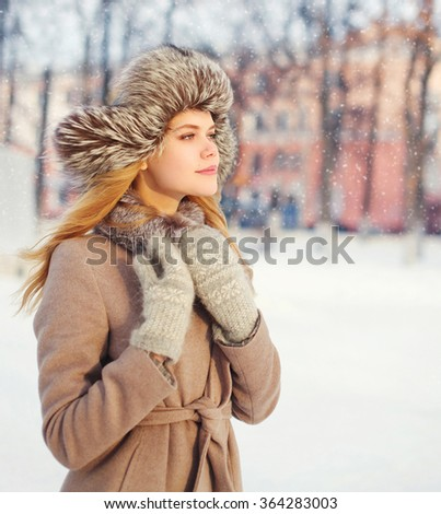 Portrait beautiful young woman wearing a coat and hat over snowflaskes in winter day - stock photo