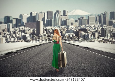 Portrait beautiful young woman with suitcase baggage walking on road talking on mobile phone isolated city skyscraper megapolis mountain skyline background. New urban life beginning adventure concept  - stock photo