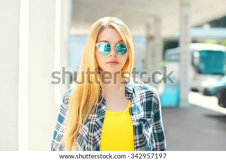 Portrait blonde young girl wearing a checkered shirt and sunglasses in city - stock photo