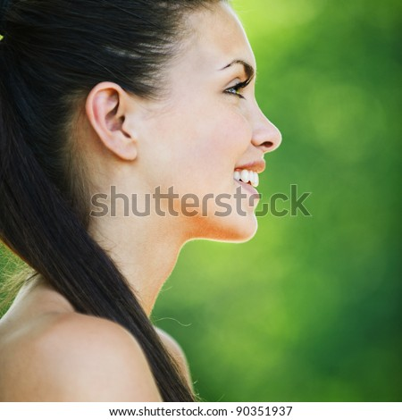 portrait charming woman profile long dark hair bare smiling background green park - stock photo