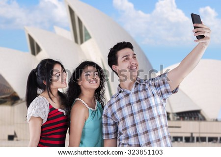 Portrait cheerful multiracial teenagers taking self portrait near the Opera House in Sydney - stock photo