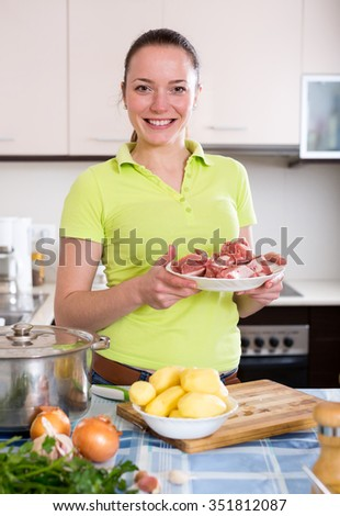 Portrait cheerful woman preparing beef ragout with potatoes for dinner - stock photo