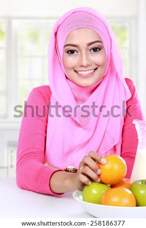portrait cheerful young muslim woman had a fruits for breakfast - stock photo