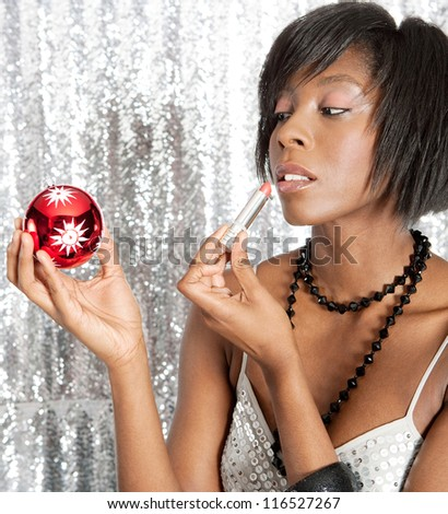 Portrait close up of an attractive black woman using a Christmas bar ball reflection to apply her lipstick while standing in front of a silver sequins background. - stock photo