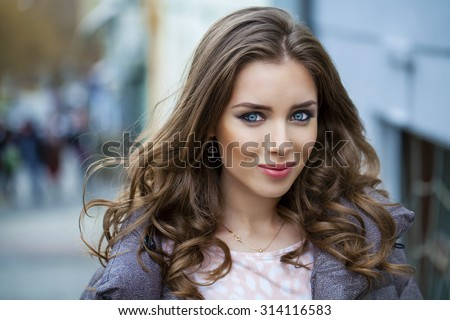 Portrait close up of young beautiful brunette woman, on spring street background - stock photo