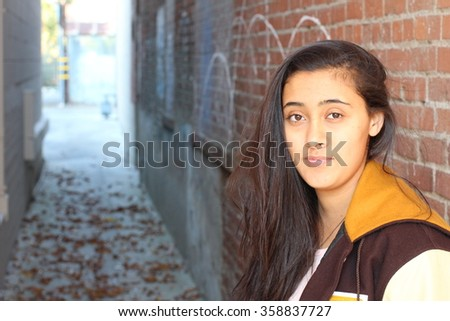 Portrait close up of young beautiful ethnic girl on brick wall background with copy space on the left side - stock photo