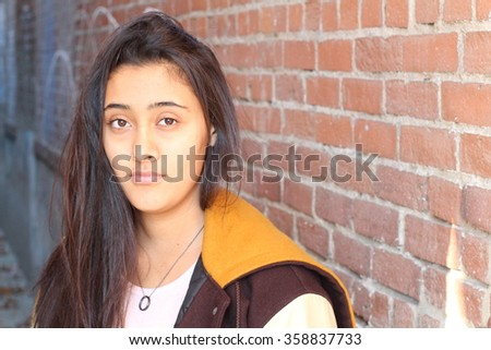 Portrait close up of young beautiful ethnic girl on brick wall background with copy space on the right side - stock photo