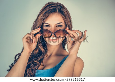 Portrait closeup attractive beautiful happy  successful young woman girl holding sunglasses smiling at camera isolated green background wall. Positive human emotion facial expression feeling attitude - stock photo