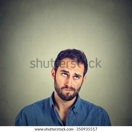 Portrait closeup funny confused skeptical man thinking looking up isolated on gray wall background with copy space above head. Human face expressions, emotions, feelings, body language - stock photo