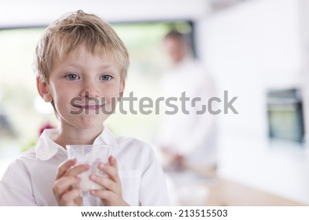 portrait closeup of a boy who drinks a glass of milk in family kitchen - stock photo