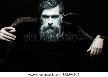 Portrait closeup view of one halloween holiday celebration character senior man with spooky painted face of zombi and long white lush beard holding animal antlers black and white, horizontal picture - stock photo