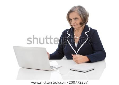 Portrait: competent senior businesswoman sitting at desk with computer. - stock photo