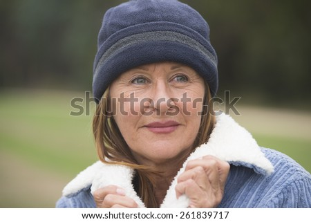 Portrait confident attractive mature woman outdoor, wearing warm bonnet and wool jacket, blurred green background. - stock photo