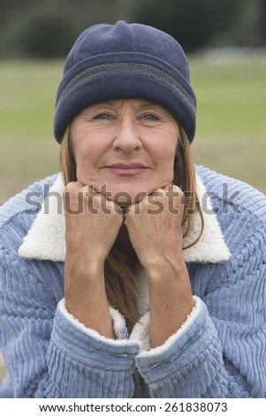 Portrait confident attractive mature woman outdoor, wearing warm bonnet and wool jacket, relaxed resting chin on hands blurred green background. - stock photo
