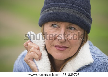 Portrait confident attractive mature woman outdoor, wearing warm bonnet and wool jacket, serious look, blurred green background. - stock photo