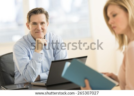 Portrait confident businessman with female colleague at desk in office - stock photo