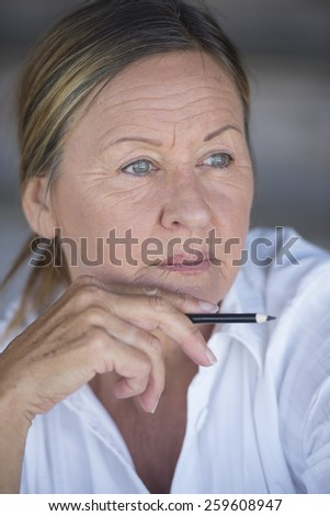 Portrait confident creative attractive mature business woman, thoughtful, serious, relaxed, with pen in hand, blurred background. - stock photo