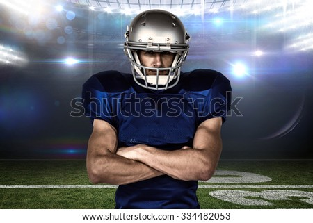 Portrait confident of American football player with arms crossed against american football arena - stock photo