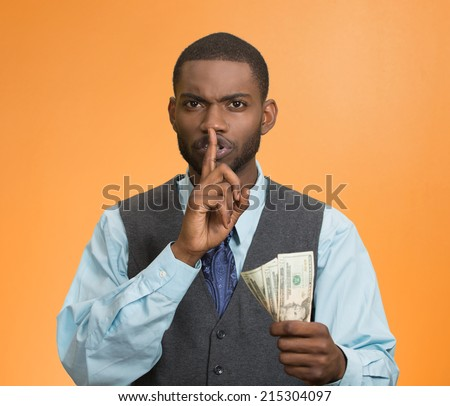 Portrait corrupt guy, businessman holding dollar bills in hand showing shhh sign finger to lips isolated orange background. Bribery concept politics business diplomacy. Face expression, body language - stock photo