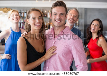 Portrait couple embracing each other in restaurant and friends standing in background - stock photo