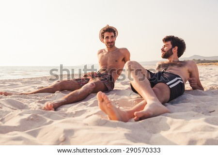 Portrait. Couple of male friends at sunset on the beach on a day of rest summer vacation together, after spending a day of relaxation and fun. - stock photo