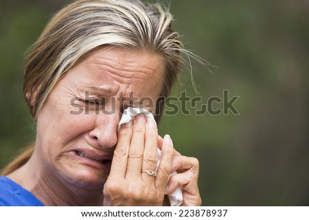Portrait crying mature woman in grief, with sad unhappy, stressed emotional facial expression, suffering painful depression, tissue in hands, outdoor blurred background. - stock photo