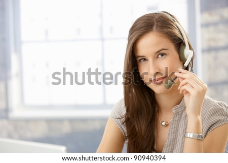 Portrait customer service operator girl wearing headset, smiling at camera, copyspace.? - stock photo