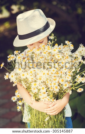 Portrait cute boy in a hat with big white bouquet of chamomiles. Summertime. Toning image - stock photo