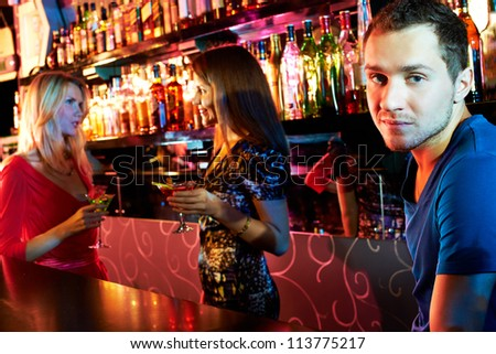 Portrait cute guy looking at camera at party with two girls chatting on background - stock photo