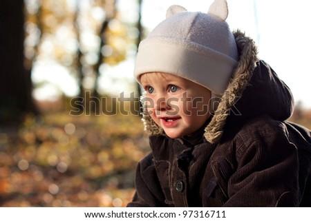 Portrait cute joyful child against a background of golden nature. Blurred background - stock photo