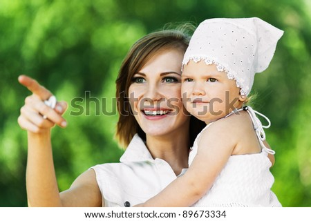 portrait cute young woman holding arms child smiling background summer green park - stock photo