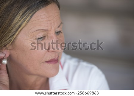 Portrait elegant attractive mature woman with sad lonely concerned depressed expression, blurred background, copy space. - stock photo