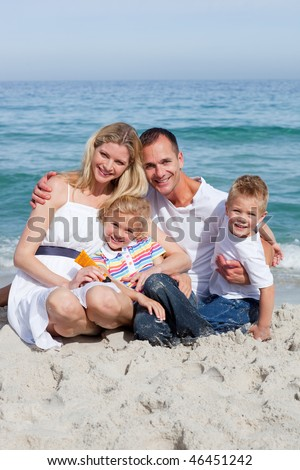 Portrait f a cheerful family holding sunscreen at the beach - stock photo