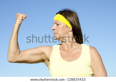 Portrait fit and healthy, confident and determined attractive looking mature woman exercising and strong biceps, isolated with blue sky as background . - stock photo