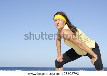 Portrait fit and healthy, confident and determined attractive looking mature woman exercising at beach, isolated with ocean and blue sky as background and copy space. - stock photo