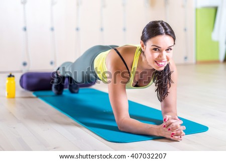 portrait fitness training athletic sporty woman doing plank exercise in gym or yoga class concept exercising workout aerobic - stock photo