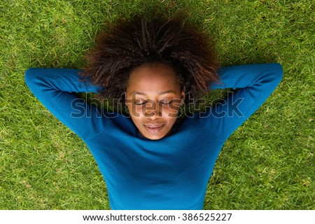 Portrait from above of a young african woman lying on grass sleeping - stock photo