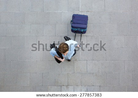 Portrait from above of a young man walking with luggage at airport - stock photo