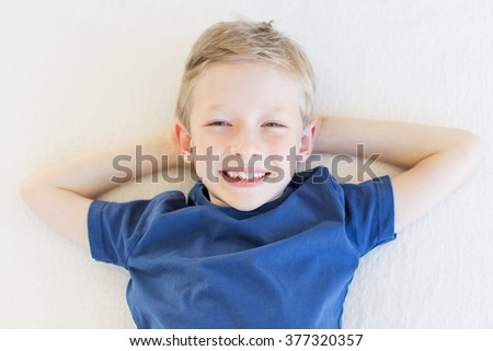 portrait from above of beautiful smiling boy expressing positive emotions lying down and relaxing during vacation - stock photo